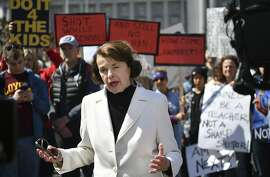 """Sen. Dianne Feinstein, D-Calif., speaks to members of the media as crowds of people participate in the """"March for Our Lives"""" rally in support of gun control, Saturday, March 24, 2018, in San Francisco. In a historic groundswell of youth activism, hundreds of thousands of teenagers and their supporters rallied across the U.S. against gun violence Saturday, vowing to transform fear and grief into a """"vote-them-out"""" movement and tougher laws against weapons and ammunition. (AP Photo/Josh Edelson)"""