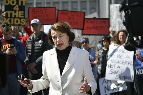 "Sen. Dianne Feinstein, D-Calif., speaks to members of the media as crowds of people participate in the ""March for Our Lives"" rally in support of gun control, Saturday, March 24, 2018, in San Francisco. In a historic groundswell of youth activism, hundreds of thousands of teenagers and their supporters rallied across the U.S. against gun violence Saturday, vowing to transform fear and grief into a ""vote-them-out"" movement and tougher laws against weapons and ammunition. (AP Photo/Josh Edelson)"