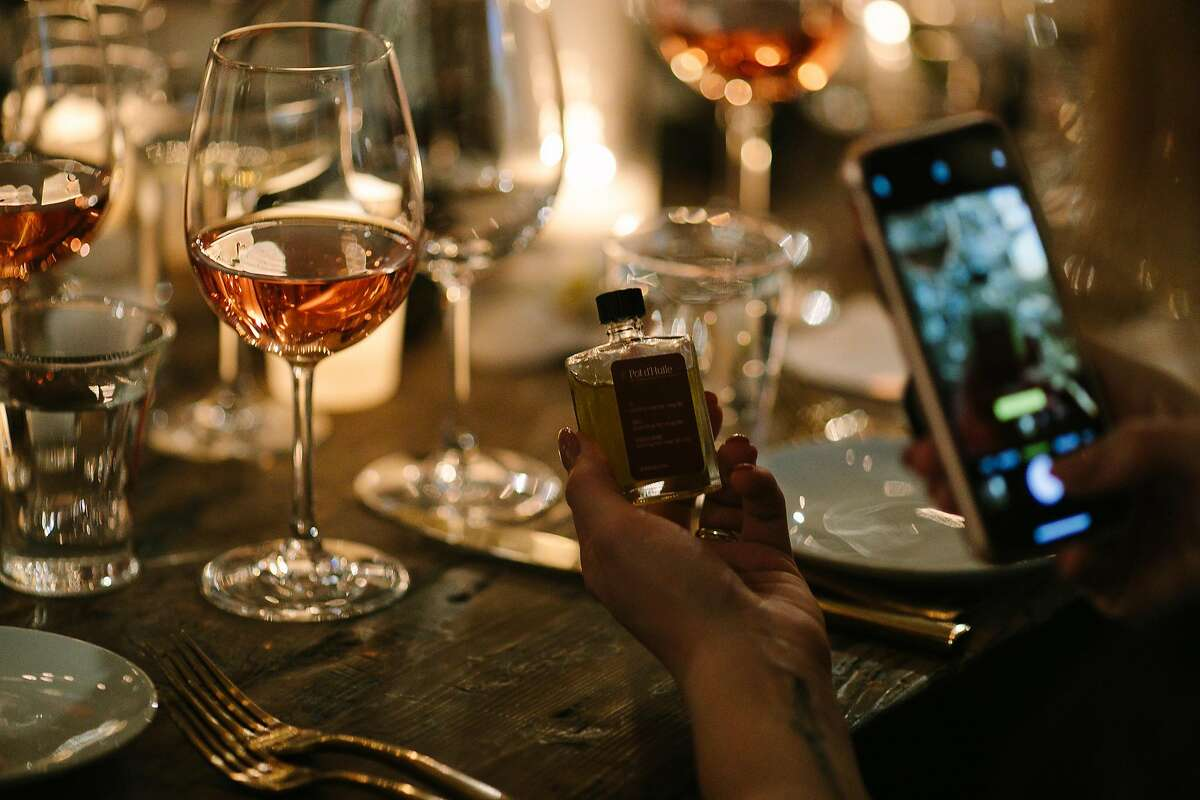 A patron takes a picture of the cannabis-infused olive oil, Pot d'Huile, before using it on her appetizers during TSO Sonoma's event in San Francisco, Calif. Saturday, Feb. 10, 2018.
