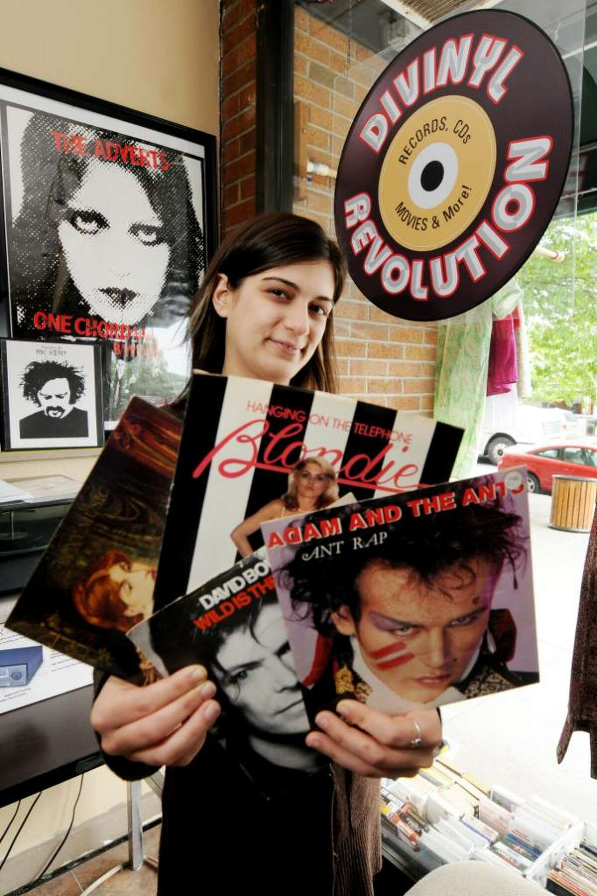 Brittany Nasser, the owner of Divinyl Revolution on Broadway in Saratoga Springs, on Tuesday, May 18, 2010, holds jackets from some hard-to-find seven-inch records available in her shop. Brittany was an employee when the shop under the old owners was called