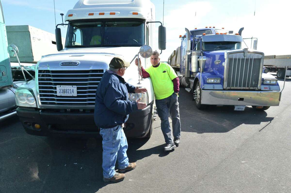 Independent truck drivers Ed Owens and Joe Riamond stand by their rigs after driving from York, Pa. to the public docks at Veterans Memorial Park on Monday April 9, 2018 in Norwalk Conn. Six 18-wheeler flatbed trucks arrived at docks on Monday, each carrying massive plastic foam-filled concrete sections that will form the new visitors? docks at the public boat-lunch. The docks arrived from Bellingham Marine's plant in York, Pa., and will be installed by Terry Construction over the next several weeks.
