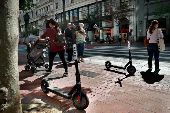 Two Bird scooters parked along Market St. as pedestrians wait at  the crosswalk as seen on Mon. April 9, 2018, in San Francisco, Calif.