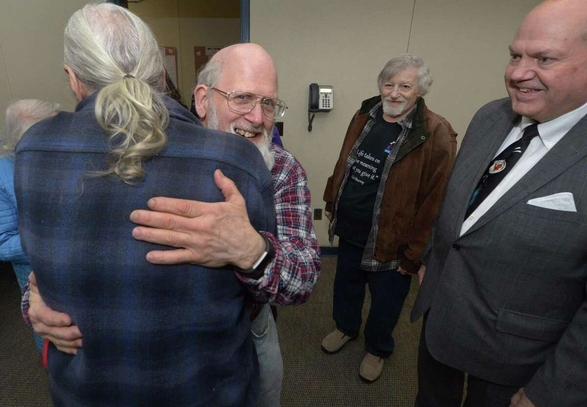 Friends and family, including brothers Bob Tolles and Terry Tolles and cousin Allen Church, are greeted Billy Tolles, center, as he marks his 20-year career at the Norwalk Public Library with an anniversary party on Friday.