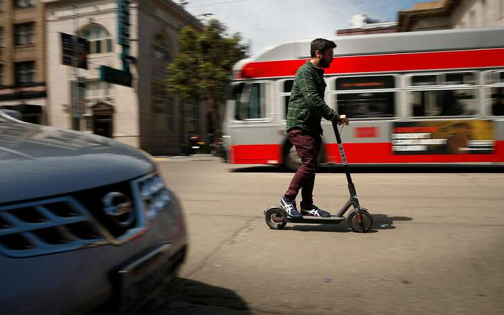 Cruising down Mission st. on a Bird scooter as seen on Mon. April 9, 2018, in San Francisco, Calif.