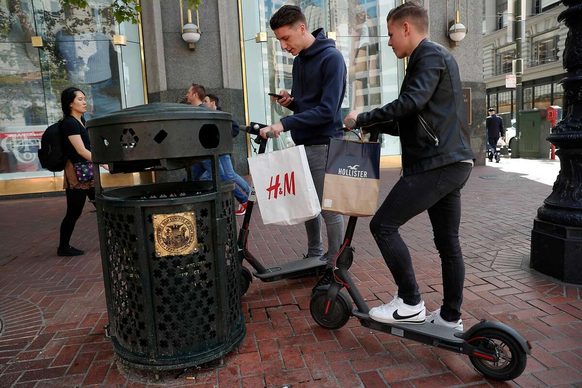 Leo Dubler, (left) and Bastien Ruch, visiting from Switzerland check out two Bird scooters for the first time, along Market st. in San Francisco.