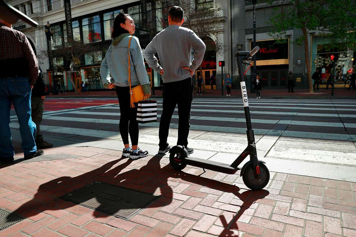 A Bird scooter parked along Market St. as pedestrians wait at the crosswalk as seen on Mon. April 9, 2018, in San Francisco.