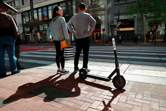 A Bird scooter parked along Market St. as pedestrians wait at the crosswalk as seen on Mon. April 9, 2018, in San Francisco, Calif.