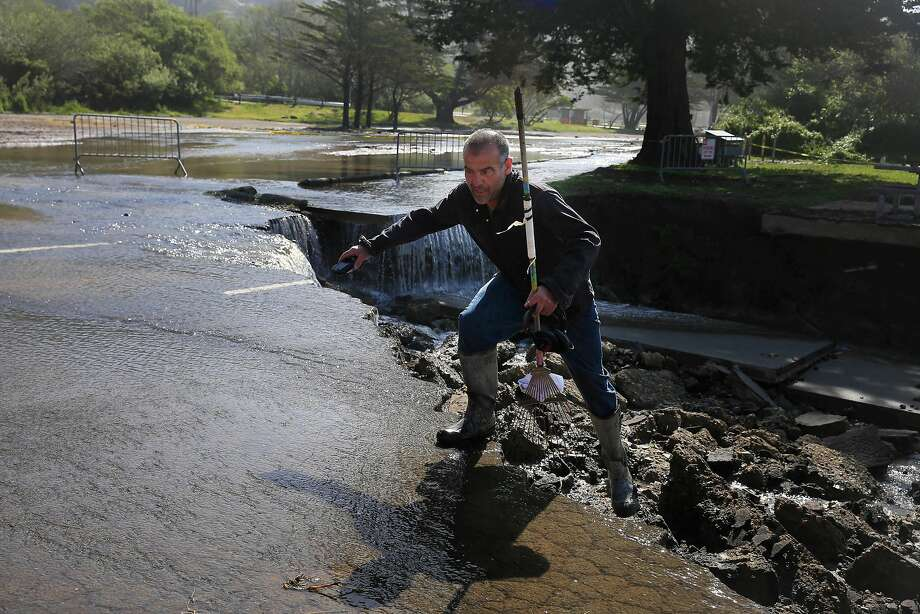 Dino Colombo of Stinson Beach climbs onto the asphalt where part of the north end of the Stinson Beach parking lot collapsed over the weekend after heavy rains. Photo: Lea Suzuki / The Chronicle