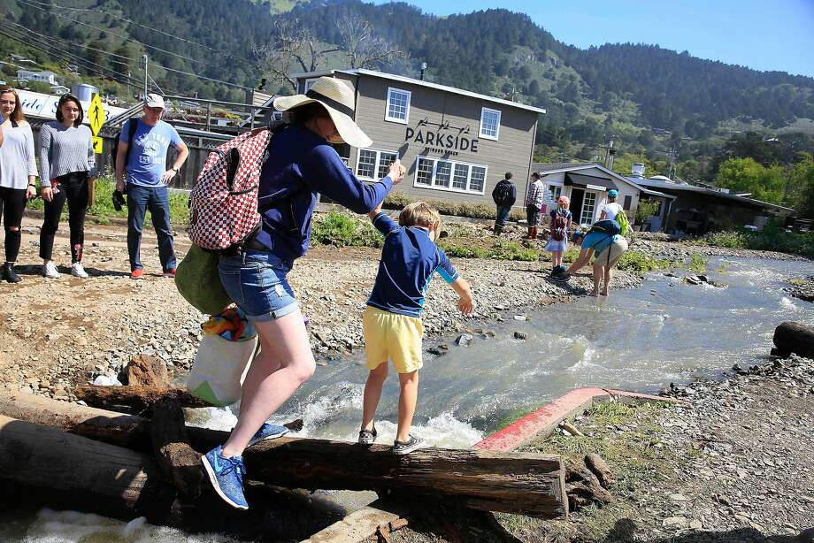 En route to a day outing to the beach, Abby Costello holds the hand of Renzo Mindel, 4, as they make their way across a log over water spilling out of Easkoot Creek and through the Stinson Beach parking lot, part of which collapsed after last week's rains. Photo: Lea Suzuki / The Chronicle