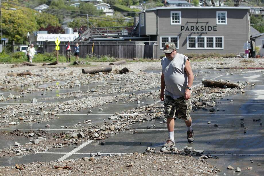 Greg Staude of Bolinas walks around debris in the Stinson Beach parking lot.Nearly half of the 316 parking spaces in the north lot were destroyed. Photo: Lea Suzuki / The Chronicle