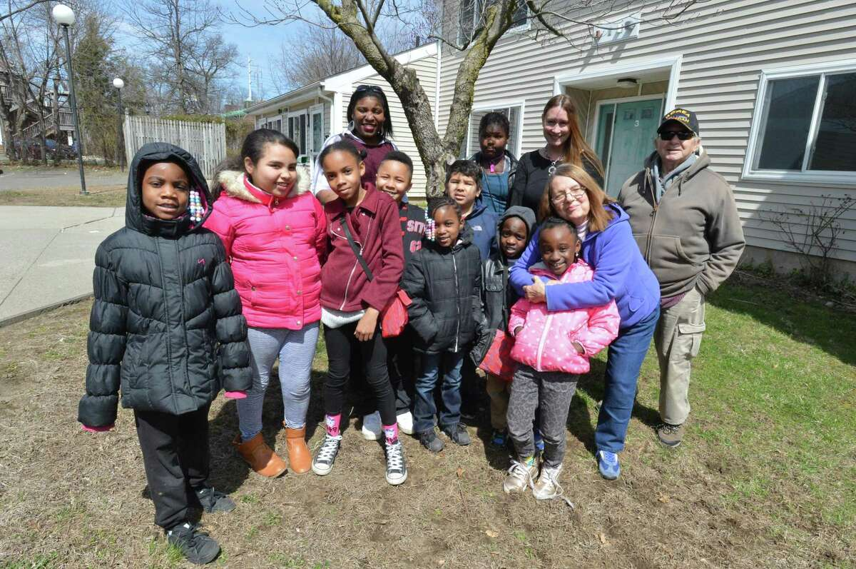 Norwalk Community College Biology Professor Erica Kipp stands with kids in the after school learning center program and and their director Wendy Gerbier and some residents outside at Ludlow Commons on Monday April 9, 2018 in Norwalk Conn. A TD Green streets grant will help the kids in the program beautify the area and plant some trees at Roodner Court.