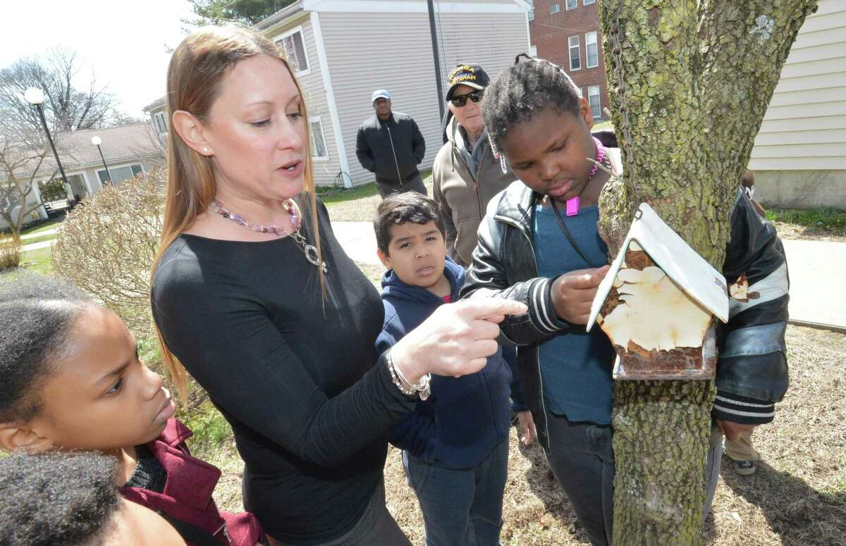 Norwalk Community College Biology Professor Erica Kipp shows some of the kids in the after school learning center program a birdhouse on one of the trees outside in the courtyard at Ludlow Commons on Monday April 9, 2018 in Norwalk Conn. A TD Green Streets grant will help the kids in the program beautify the property and plant trees at Roodner Court.