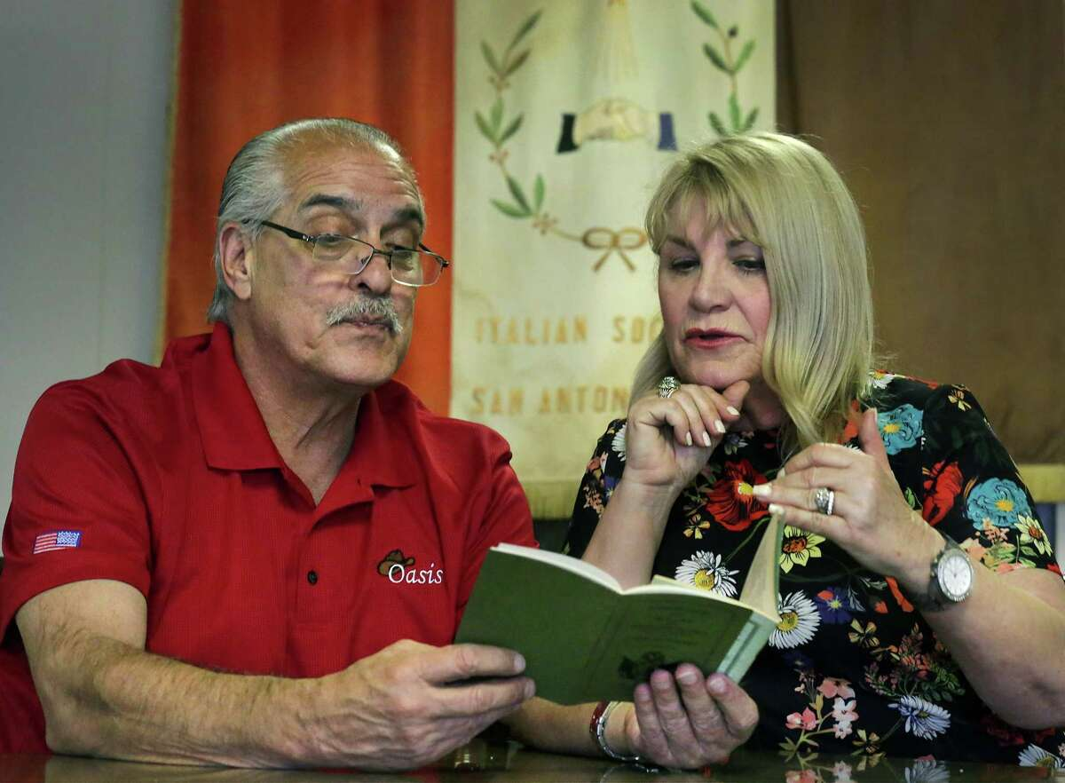 Sam Guido, left, Christopher Columbus Italian Society chairman of the Board, and Dawn Brooks Baamonde, one of the first women to be allowed to join the previously all-male group, read through a copy of the old bylaws of the society on Monday. The wording was changed to permit women to join.