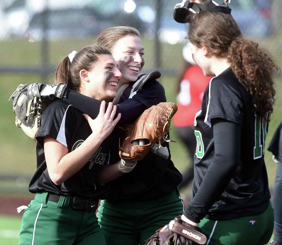 Guilford's Ava Gladwin, left, and Leah Kornguth, center, celebrate after a double play to get them out of an inning against Sacred Heart Academy on Monday. Photo: Arnold Gold / Hearst Connecticut Media / New Haven Register
