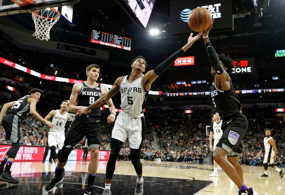 San Antonio Spurs guard Dejounte Murray (5) grabs for a rebound between Sacramento Kings guard Bogdan Bogdanovic (8) and guard De'Aaron Fox (5) during first half action Monday April 9, 2018 at the AT&T Center. Photo: Edward A. Ornelas, San Antonio Express-News / © 2018 San Antonio Express-News