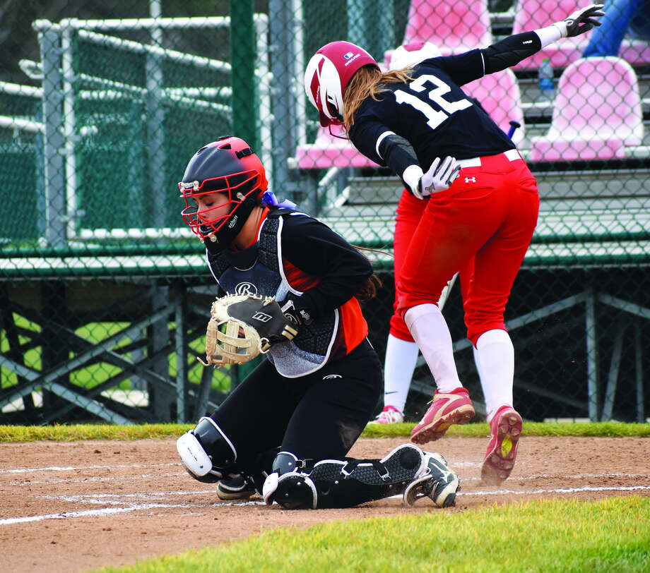 Edwardsville catcher Taryn Brown catches a throw to the plate as Chatham Glenwood's Olivia McClintock scores the first run of the game in the opening inning on Monday.