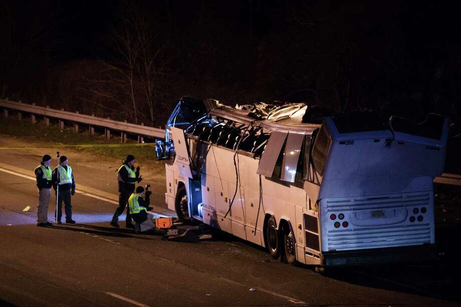 A bus that was carrying teenage passengers sits on the side of a highway after it hit an overpass on the Southern State Parkway in Lakeview, N.Y., Monday, April 9, 2018. The charter bus carrying teenagers returning from a spring break trip struck a bridge overpass on Long island, seriously injuring several passengers and mangling the entire length of the top of the bus. (AP Photo/Kevin Hagen) Photo: Kevin Hagen / FR170574 AP