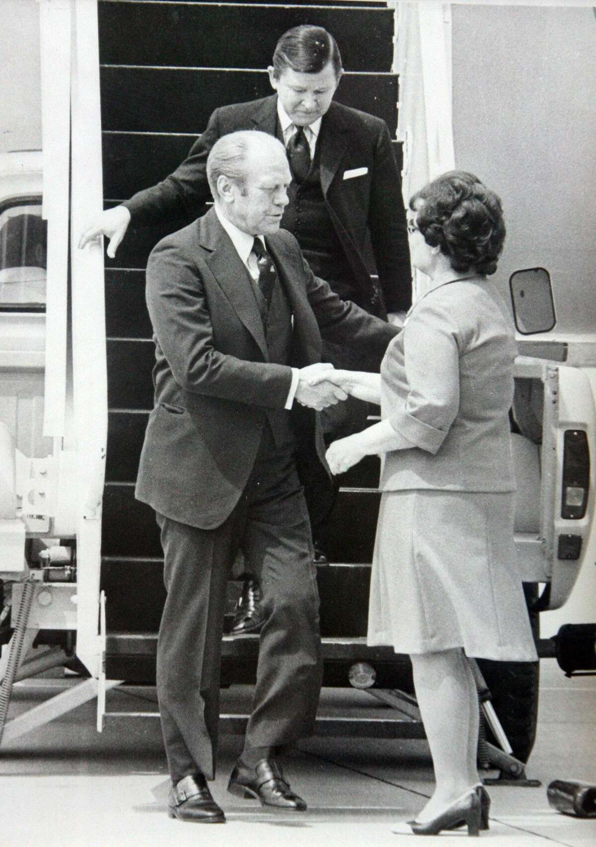 President Gerald Ford is greeted by San Antonio Mayor Lila Cockrell as Sen. John Tower walks down to the tarmac during a visit to San Antonio in 1976.