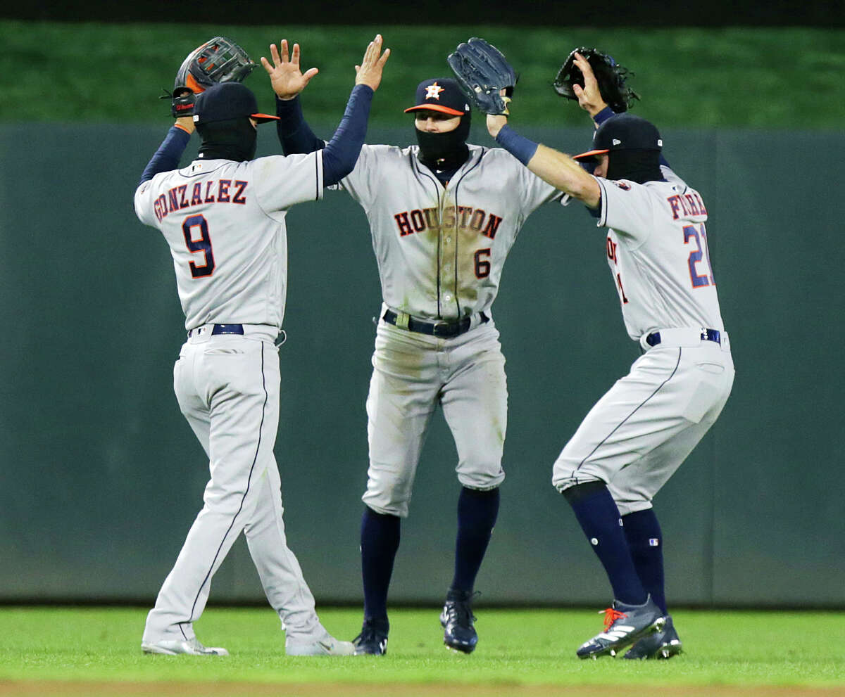 Houston Astros outfielders Marwin Gonzalez (9), Jake Marisnick (6) and Derek Fisher (21) celebrate after defeating the Minnesota Twins 2-0 during a baseball game, Monday, April 9, 2018, in Minneapolis. (AP Photo/Andy Clayton-King)