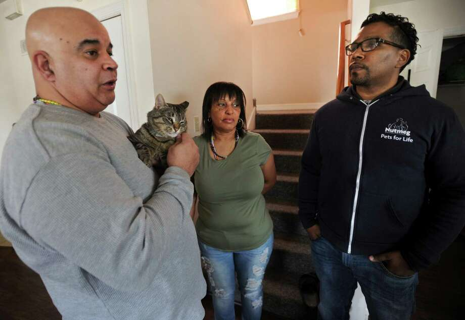 Christopher Keith, right, community outreach manager for the Humane Society's Pets for Life program, meets with Chico Gavillan and Millie Navarro and Rocky, one of the former stray cats they've adopted in their home on Shelton Street in Bridgeport, Conn. on Tuesday, March 27, 2018. Pets for Life provides free spay and neutering services through community outreach in specific zipcodes. Photo: Brian A. Pounds / Hearst Connecticut Media / Connecticut Post