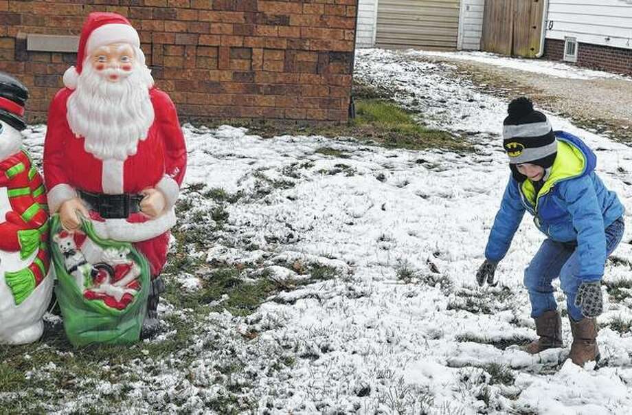 Jayse Hart, 5, prepares to throw a snowball at the Santa decoration in his front yard on South East Street. His mom and her fiancé put out the decoration — along with one of Frosty the Snowman — to make light of the snow that fell Sunday evening into Monday. Photo: Samantha McDaniel-Ogletree | Journal-Courier