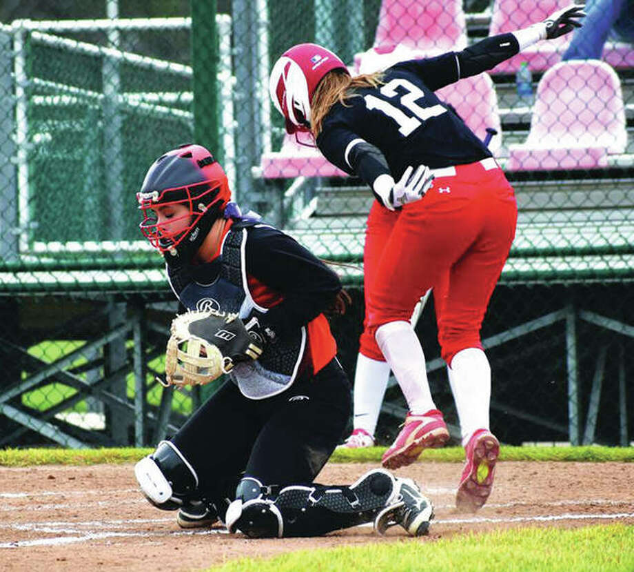 Edwardsville catcher Taryn Brown (left) receives a throw to the plate too late to get Chatham Glenwood's Olivia McClintock, who scores the first run of the game in the opening inning Monday at the District 7 Sports Complex in Edwardsville. Glenwood won 3-0 to hand the Tigers their first shutout loss at home since 2004. Photo: Matthew Kamp / Hearst Newspapers