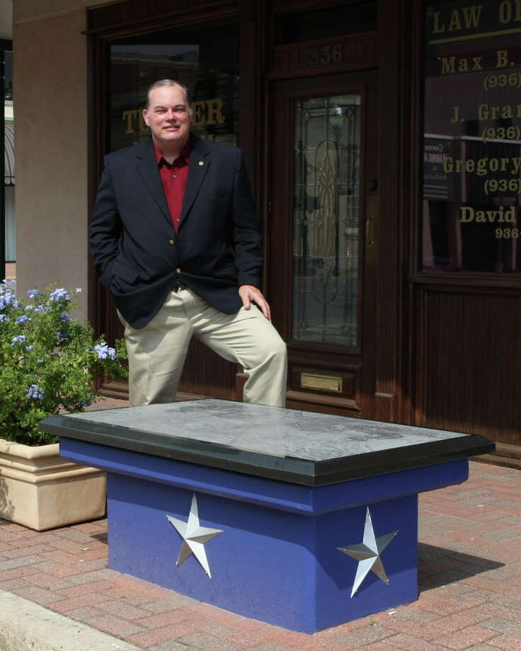 Mark C. Clapham poses with the Art Bench he designed in downtown Conroe. Following his death from cancer in January 2012, his art collection was donated to the Heritage Museum of Montgomery County. On Saturday from 5 to 8 p.m. the museum will have an exhibit of his artwork including some pieces that have never before been seen by the public.