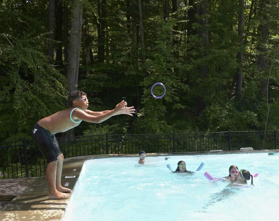 Josh Oliveira, 11, reaches for a tossed ring while swimming at the New Pond Farm summer camp on Wednesday afternoon, August 9, 2017, in Redding, Conn. Photo: H John Voorhees III / Hearst Connecticut Media / The News-Times