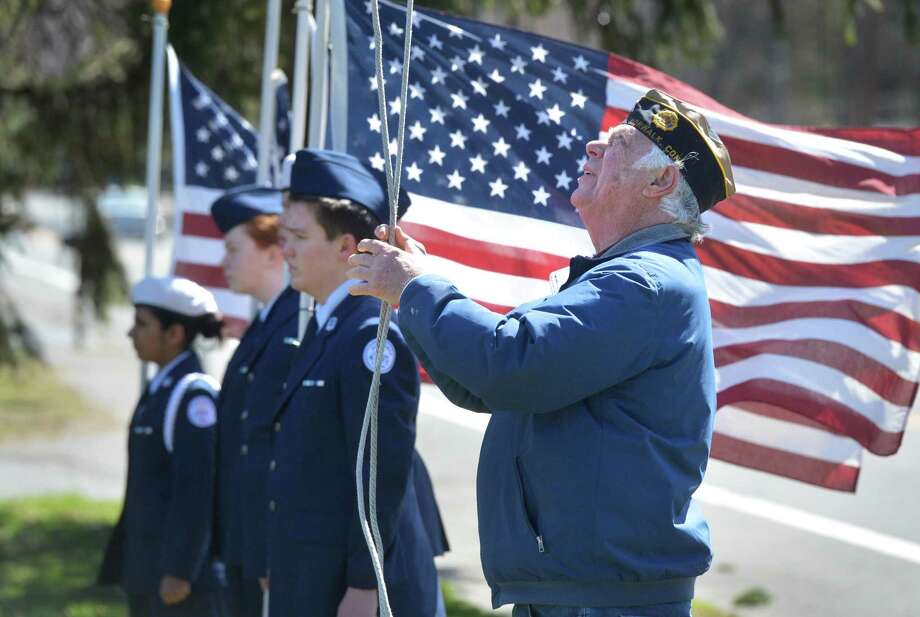 Acting Sergeant at Arms John Sullivan raises the flag for the Veteran of the Month during a ceremony at the Frank C. Godfrey American legion Post 12 in Norwalk on Sunday. The honored veteran for April is Cpl.Paul Bonenfant, who served from 1941 to 1945 in Europe. Born in Canada, Paul received the Good Conduct Medal, American Theatre Campaign Ribbon, the Victory Medal, and the European African Middle Eastern Theatre Campaign Ribbon. Photo: Alex Von Kleydorff / Hearst Connecticut Media / Norwalk Hour