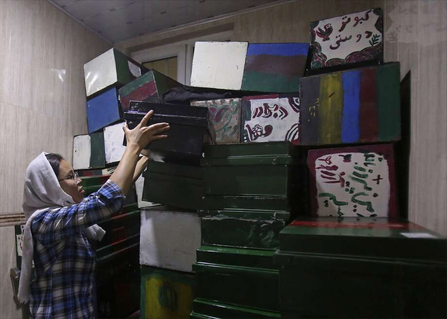 "Zahra Hossaini, a member of the Afghanistan Human Rights and Democracy Organization, arranges ""memory boxes,"" stored in a room in Kabul. Photo: Rahmat Gul / Associated Press"