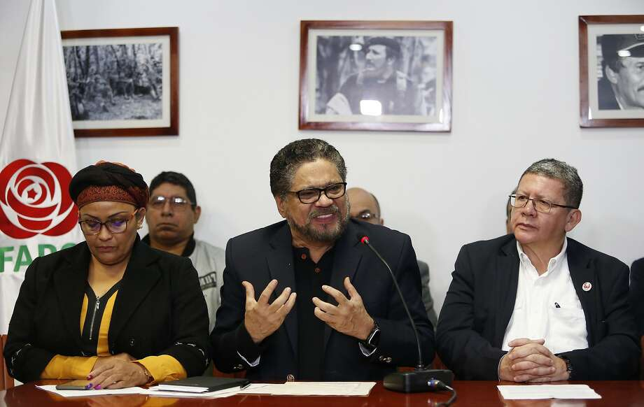 Ivan Marquez, a former leader of the Revolutionary Armed Forces of Colombia, FARC, center, gestures as he speaks to the media as Victoria Sandino, left, and Pablo Catatumbo, right, listen during a press conference in Bogota, Colombia, Tuesday, April 10, 2018. Seuxis Hernandez, a blind rebel ideologue best known by his alias Jesus Santrich, was picked up Monday at his residence in Bogota on charges that he conspired with three others to smuggle several tons of cocaine into the U.S. with a wholesale value of $15 million. (AP Photo/Fernando Vergara) Photo: Fernando Vergara / Associated Press