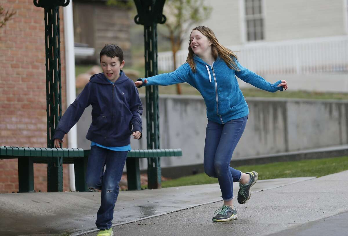 In this April 6, 2018, photo, Caleb Coulter, 10, left, and his sister Kendra, 12, play tag during a visit to the Place Heritage Park in Salt Lake City. Critics say letting children strike out on their own can expose them to serious dangers. But lawmakers and advocates in several states say the protective pendulum has swung too far. They want to send a message that parents who raise their children in a healthy environment can grant them more freedom. Amy Coulter, mother of Caleb and Kendra, said she doesn't call herself a free-range parent. But she does avoid intervening with teachers on her older children's grades and encourages her children to use their own money to buy things at the grocery store. (AP Photo/Rick Bowmer)