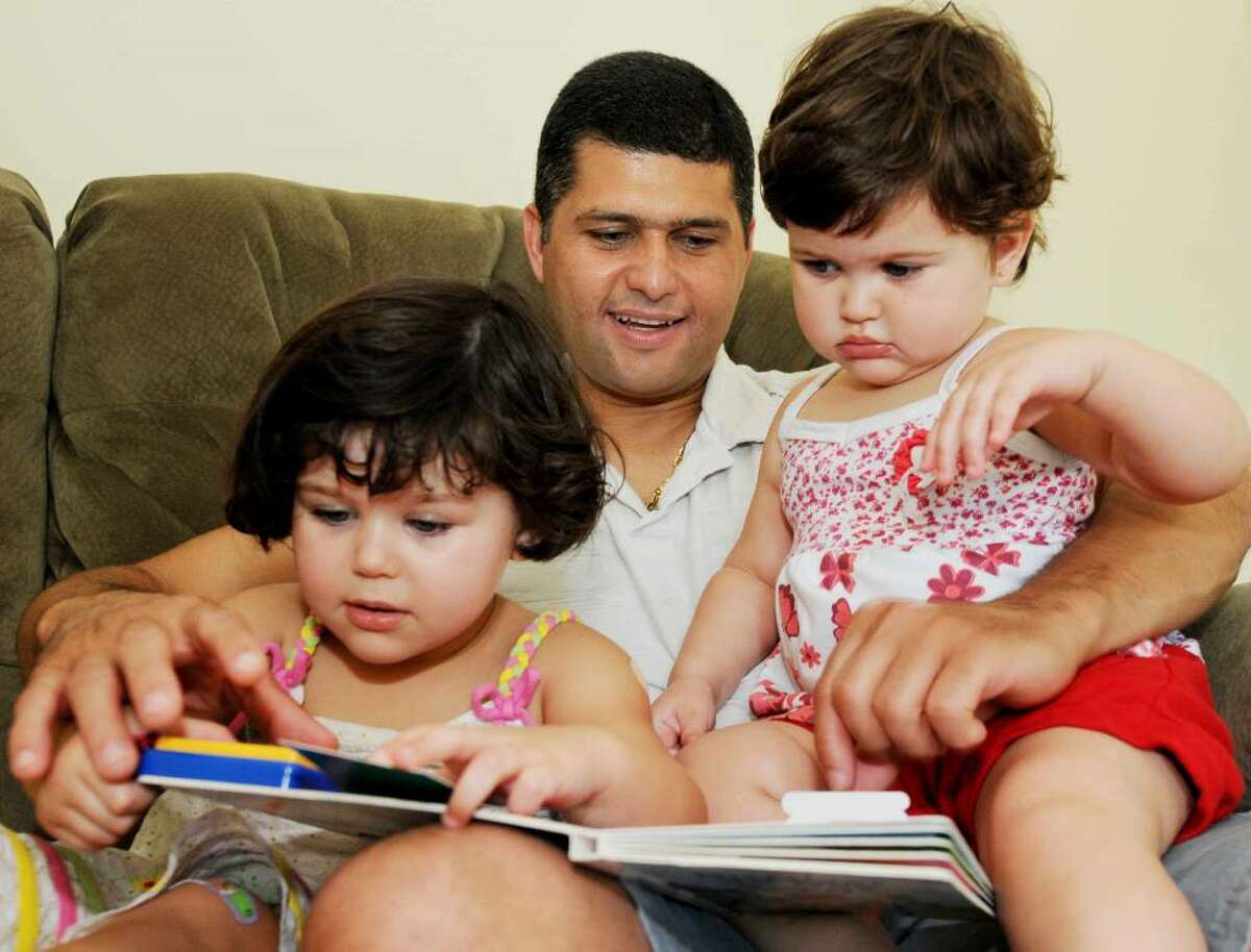 Marcio Ferreira reads to his two daughters, Milla Voigt, 2, left, and Fernanda Voigt, 15 months, in their Clifton Park home. The Brazilian, who came to America 9 years ago speaking only Portuguese, began taking the English Language Learners class at the Saratoga branch of Literacy New York?Greater Capital Region a few years ago. (Luanne M. Ferris / Times Union)