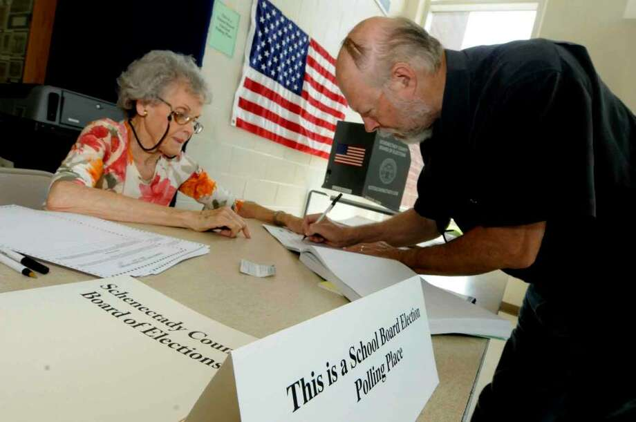 Gary Kline signs in to vote, assisted by election inspector Blanche Gray, during a budget revote at Schenectady High School on Tuesday. ( Michael P. Farrell / Times Union ) Photo: MICHAEL P. FARRELL