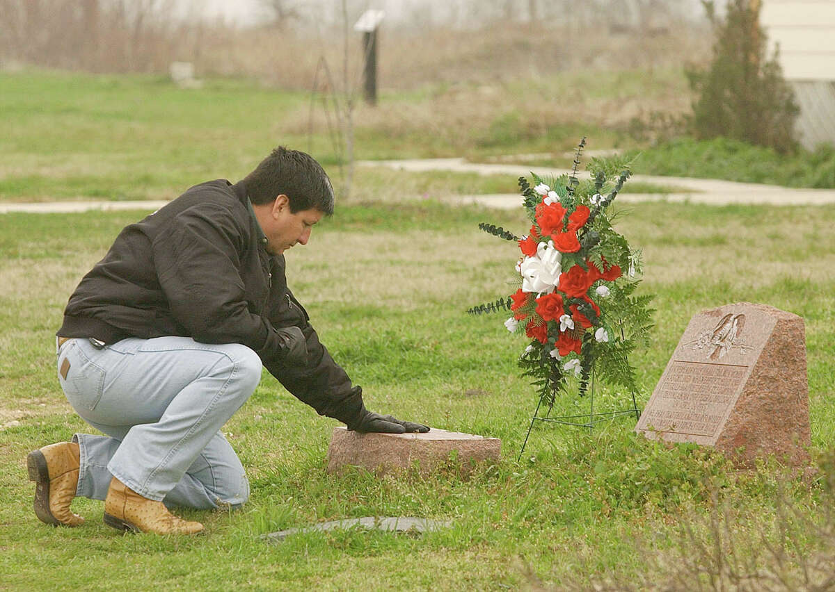 Robert Rodriguez, a former special agent with the Bureau of Alcohol, Tobacco, Firearms and Explosives, places his hand on a marker in Waco, Texas, Friday, Feb. 28, 2003. The marker memorializes four fellow agents who died while attempting to execute a search warrant on the New Mount Carmel Center. Rodriguez was in the compound when Koresh learned that federal agents were en route, and tried to warn his supervisors that agents had lost the element of surprise.