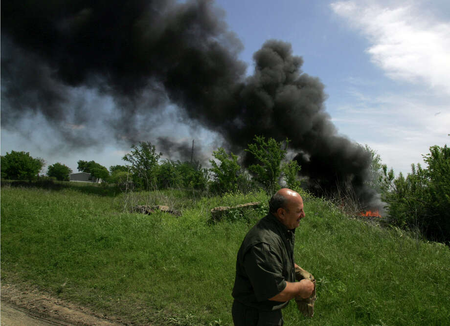Charles Pace, leader of The Branch, The Lord of Righteousness sect of the Branch Davidians, walks past burning remnants of David Koresh's building near Waco, Texas, on the anniversary of the end of the armed standoff on Thursday, April 19, 2007. Nearly 80 people died in a 1993 blaze after an armed standoff with federal agents. The fire, meant to clear debris, was started at 12:15 p.m., the same time the inferno that ended the standoff started. Photo: LM Otero/AP