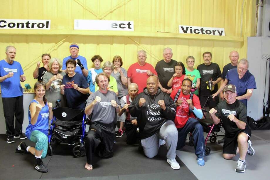 A group of Rock Steady Boxing members and coaches pose during a class break in Kingwood on Tuesday, April 3. Photo: Melanie Feuk / Melanie Feuk