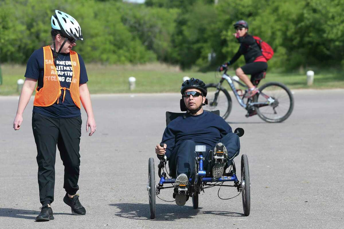 Recreational therapist Mary Phillips works with Carlos Barrera, Jr., trying out a recumbent trike during a three-day cycling camp for wounded, ill and injured service members and veterans at McAllister Park, Tuesday, April 10, 2018. South Texas VA Recreation Therapy Service partnered with Operation Comfort to host it. The camp started on Monday and provided them an opportunity to ride adaptive cycles to meet their disability. For many, riding a standard bicycle is difficult due to neurological or physical injuries that affect balance and/or mobility. Therapists have found cycling benefits include improved fine motor skills, increased immune system activity, reductions in blood pressures, pain, social anxiety and it also prevents social isolation and depression. Operation Comfort also host weekly bicycle rides on Wednesday.