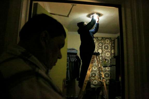 Tito Solifona (right), maintenance technician, replaces old bulbs with new LED bulbs in James Monson's (not shown) unit at a community housing development run by Swords to Plowshares on Tuesday,  April 10,  2018, in  San Francisco, Calif.  San Francisco's Department of the Environment is providing 100,000 free LED lightbulbs to city residents, particularly disadvantaged ones under a new program.