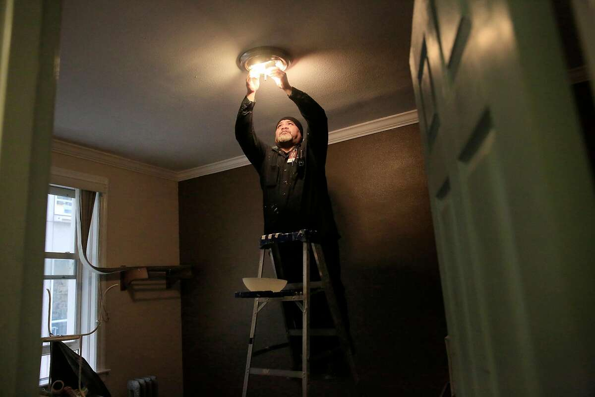 Tito Solifona, maintenance technician, replaces old bulbs with new LED bulbs in a vacant unit at a community housing development run by Swords to Plowshares on Tuesday, April 10, 2018, in San Francisco, Calif. San Francisco's Department of the Environment is providing 100,000 free LED lightbulbs to city residents, particularly disadvantaged ones under a new program.