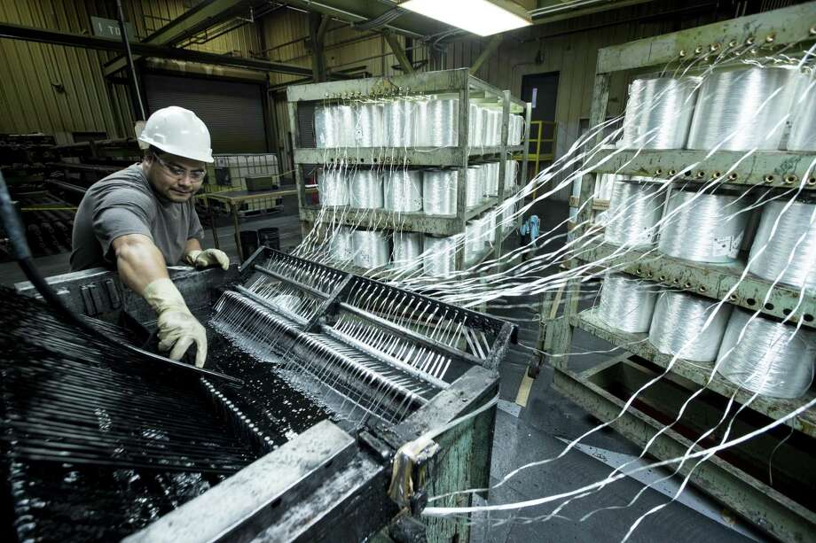 Oscar Peralta cleans parts of a resin bath at Champion Fiberglass on Tuesday, April 10, 2018, in Houston. The fibrerglass manufacturer is seeing an uptick in business sincer news of tariffs on foreign steel and aluminum, and expanding its production as demand for fiberglass pipes and conduit rises. ( Brett Coomer / Houston Chronicle ) Photo: Brett Coomer, Staff / Houston Chronicle / © 2018 Houston Chronicle
