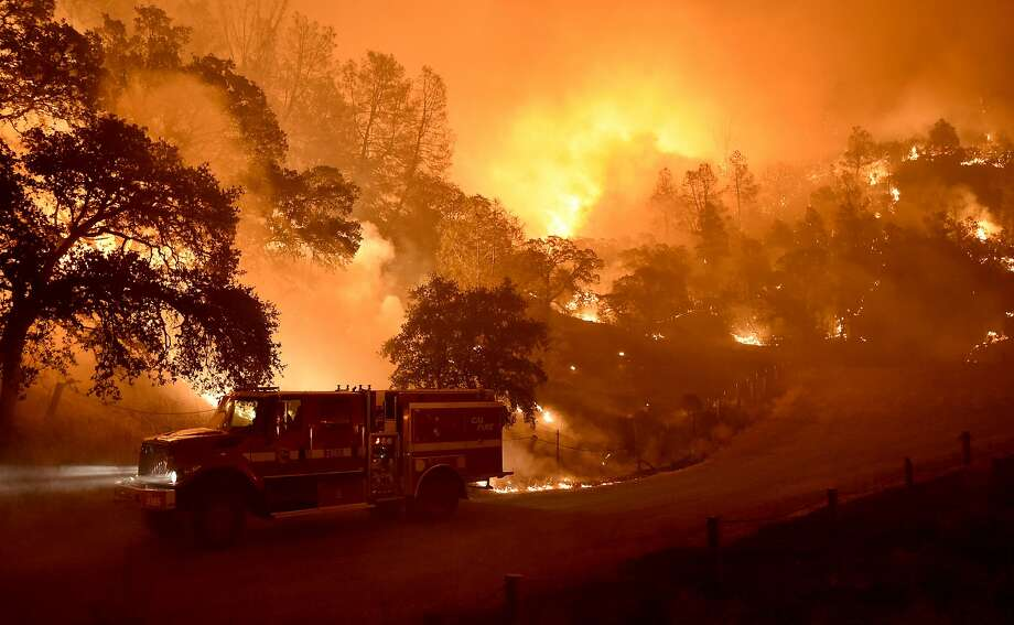 A Cal Fire truck is driven away from flames as the Rocky fire burns near Clear Lake, California on August 2, 2015. The fire has charred more than 27,000 acres, and is currently only 5% contained. Photo: Josh Edelson / Getty Images