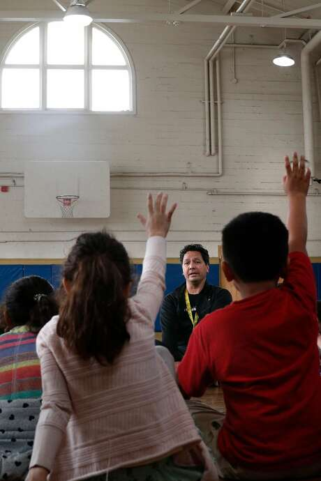 Physical education instructor Roji Behr talks with students inside the gymnasium before class where the shelter would be  at Buena Vista Horace Mann K-8 school in San Francisco. Photo: Michael Macor / The Chronicle