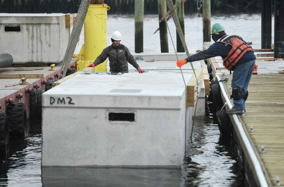 Workers with Terry Marine install the 8 ton dock sections at Veterans Memorial Park as part of a $1.5 million dock-replacement project for the David S. Dunavan Boating Center Tuesday, April 10, 2018, in Norwalk, Conn. The plastic foam-filled, concrete dock sections, each measuring 10 to 40 feet in length and weighing between 16,000 and nearly 40,000 pounds, arrived by six tractor-trailer trucks from Bellingham Marines facility in York, Pa. Photo: Erik Trautmann / Hearst Connecticut Media / Norwalk Hour