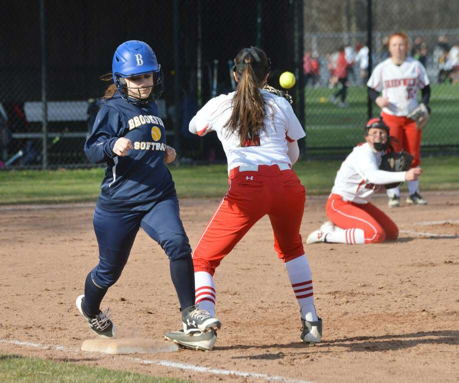 At left, Cara Lennon of Brookfield hustles as she beats out a bunt during the top of the fourth inning of the high school softball game between Greenwich High School and Brookfield High School at Greenwich, Conn., Tuesday, April 10, 2018. Photo: Bob Luckey Jr. / Hearst Connecticut Media / Greenwich Time