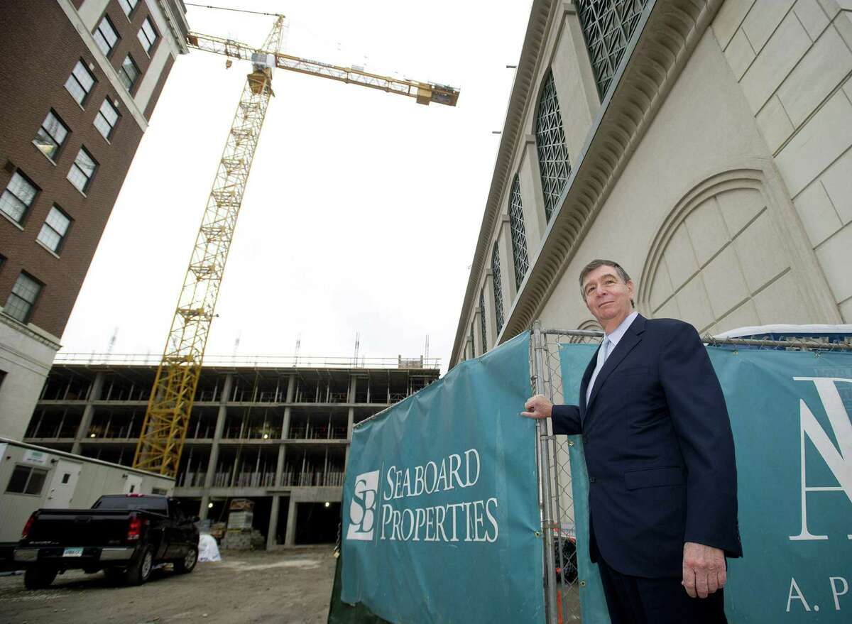 John DiMenna, president of Seaboard Properties, poses for a photo in front of the company's project on Atlantic Street in Stamford, Conn., on Nov. 25, 2014. DiMenna has been sentenced to seven years in prison for fraud perpetrated during his time leading Seaboard.