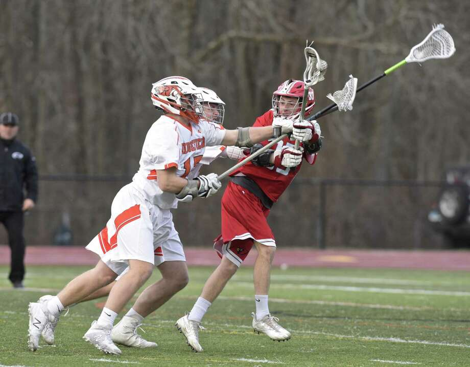 Greenwich's Leo Johnson (33) gets off a pass while being pressured by Ridgefield's Luke Marczak (13) and Noah Isaacson (17) on Tuesday in Ridgefield. Greenwich lost its third straight game in a rematch of last year's FCIAC semifinals. Lance Large, Jack Feda and Johnson each scored two goals for the Cardinals. Story on www.greenwichtime.com Photo: H John Voorhees III / Hearst Connecticut Media / The News-Times