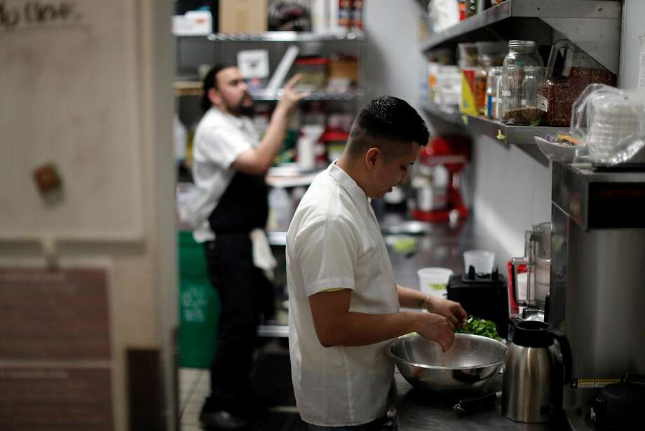 Reuben Reyna, line cook, prepares greens as Sous Chef Brock Crandall does inventory during dinner prep time at Son's Addition restaurant in San Francisco, Calif., on Tuesday, April 10, 2018. The restaurant industry is feeling new tensions surrounding ICE raids and inspections, as workers who might be undocumented are nervous of being caught in immigration sweeps. Photo: Carlos Avila Gonzalez / The Chronicle
