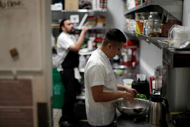 Reuben Reyna, line cook, prepares greens as Sous Chef Brock Crandall does inventory during dinner prep time at Son's Addition restaurant in San Francisco, Calif., on Tuesday, April 10, 2018. The restaurant industry is feeling new tensions surrounding ICE raids and inspections, as workers who might be undocumented are nervous of being caught in immigration sweeps.