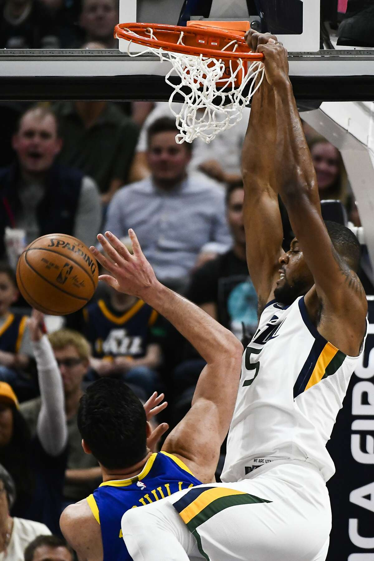Utah Jazz forward Derrick Favors (15) dunks over Golden State Warriors center Zaza Pachulia (27) in the first half of an NBA basketball game Tuesday, April 10, 2018, in Salt Lake City. (AP Photo/Alex Goodlett)